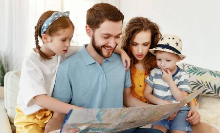 Laughing parents with little daughter and son exploring map together while making up new trip for summer vacation