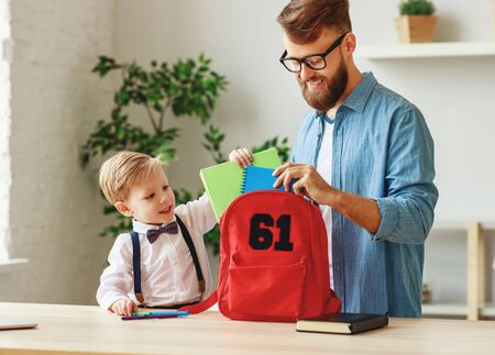 Happy little boy with father putting copybooks into backpack while standing near table at home and preparing for school