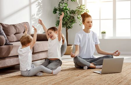 Young smiling woman sitting in lotus pose with laptop on floor and calming down while noisy kids playing in living room Imagens