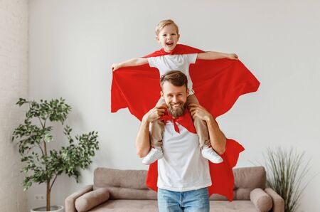 Cheerful bearded young father holding son on shoulders while having fun together dressed in red superhero cloak in living room Banque d'images