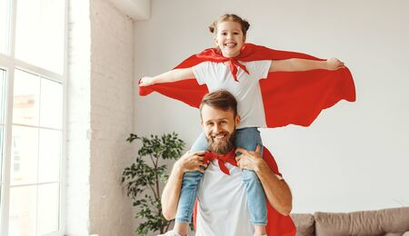 Smiling bearded young man holding cute girl on shoulders while playing superheroes together dressed in red superhero cloak in light room