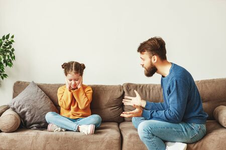 Bearded young man scolding daughter sitting on couch and gesturing while little girl sitting with legs crossed and eyes closed and covering ears
