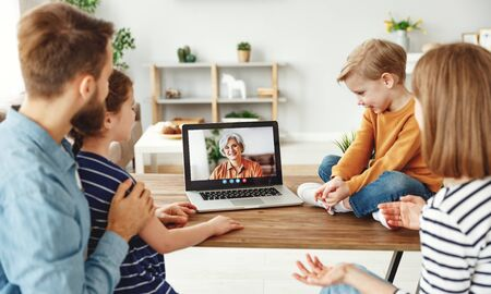 Modern parents and children sitting at table and speaking with elderly woman through video chat app on laptop while spending time at home together