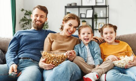 Positive smiling parents sitting on comfortable sofa with little son and daughter while enjoying movie and eating popcorn at home