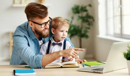 Young bearded man in eyeglasses pointing at laptop while explaining lesson to little son during online studying together at home