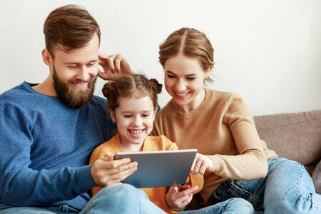 Optimistic young parents with laughing daughter in casual outfit sitting on couch browsing tablet while spending time together during sunny day