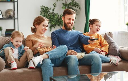Happy young parents with cute kids sitting on couch in living room at home and watching funny movie while eating popcorn and enjoying weekend together