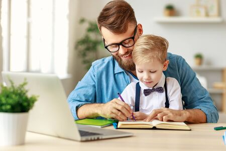 Young bearded man in eyeglasses helping smiling little boy with homework while spending time together at home