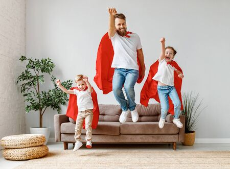 Full body of cheerful father with two children in casual clothes and red superhero cloaks jumping from couch to floor while playing heroes at home Banque d'images