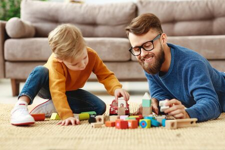 Side view of cute little boy and cheerful young man spending free time together and playing with colorful blocks on floor in living room Banque d'images