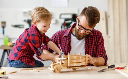 Happy little boy helping father while creating wooden toy car at workbench and enjoying time together in modern carpentry workshop 版權商用圖片 - 148070497