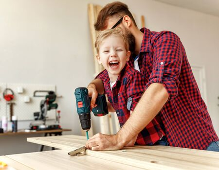 Excited little boy and young father in similar shirts holding drill together while working with wood in modern handicraft studio