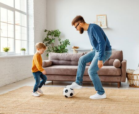 Full length cheerful boy laughing   near bearded father with ball while playing football at home together 版權商用圖片