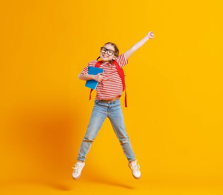Full body delighted girl in trendy casual clothes smiling and jumping with raised arm while having fun before school studies against yellow backdrop