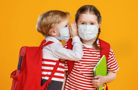 Boy in mask whispering secret into ear of classmate while studying at school during quarantine against yellow background
