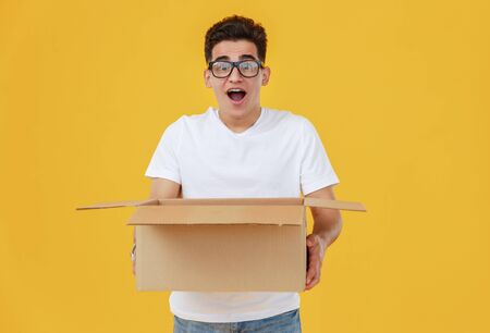Surprised ethnic young male in glasses with cartoon box with opened mouth against yellow background