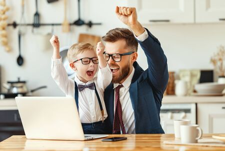 Young male entrepreneur in formal clothes and eyeglasses with little son in formal wear looking at laptop screen and celebrating successful deal while working remotely in modern apartment