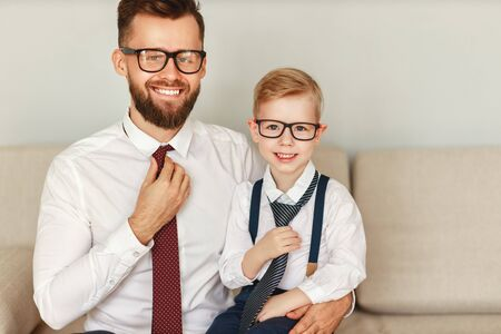 A happy bearded businessman in a strict shirt tie and glasses sits with his young son in a similar outfit on the sofa and looks at the camera with a smile
