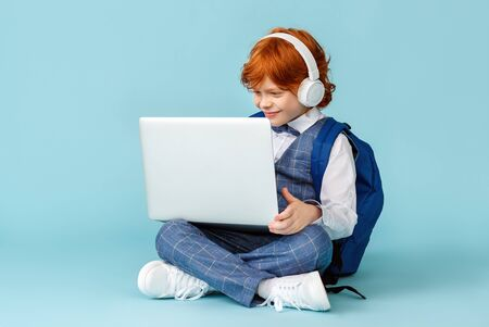 positive little red-haired schoolboy in headphones smiling and  learn remotely on modern laptop while sitting crossed legged on blue background