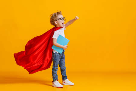 Full body boy in superhero cape smiling and raising fist up while being ready for school studies against yellow backdrop