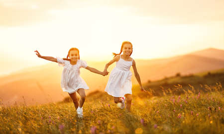 happy children sisters twin girls in white dresses run at sunset in nature in summer