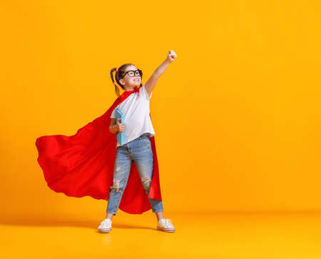 Full body girl in superhero cape smiling and raising fist up while being ready for school studies against yellow backdrop