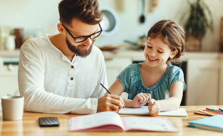 Positive young bearded man in casual clothes and glasses taking notes in copybook while explaining task to daughter during remote studies at home