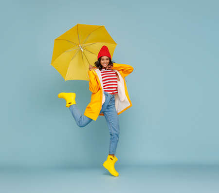 Full body happy ethnic woman in stylish outfit carrying umbrella and jumping on blue background Stockfoto