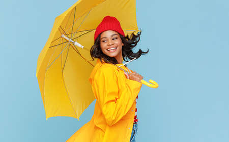 Side view of optimistic young ethnic woman in raincoat and hat carrying umbrella and looking away over shoulder while spinning around on rainy day against blue background