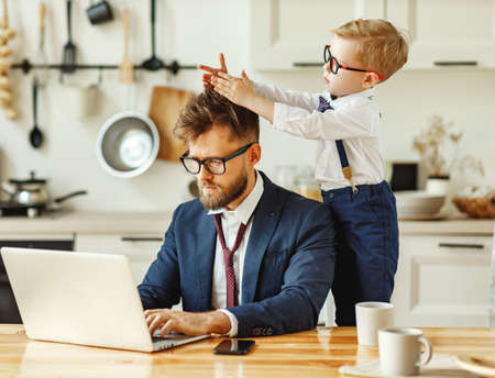 Cheerful playful kid sitting on neck of unhappy busy dad in formal wear during phone conversation and working with laptop in home kitchen Foto de archivo
