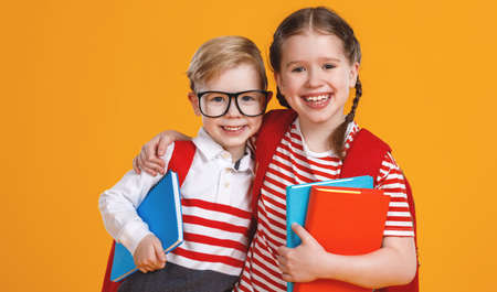 Optimistic boy and girl with textbooks hugging each other and smiling for camera during school studies against yellow backdrop