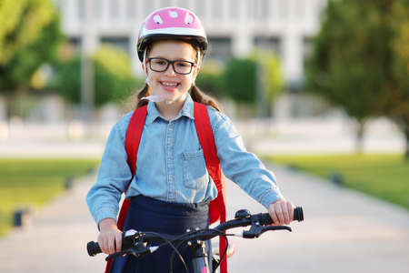 Cheerful child schoolgirl rides to school on a Bicycle in outdoor