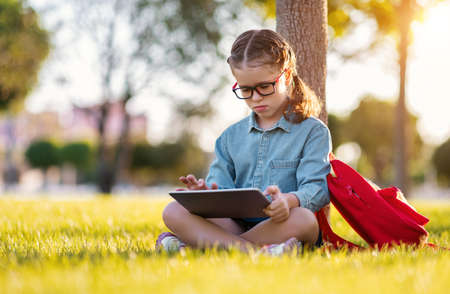 Side view of happy girl in glasses smiling and reading notes in tablet pc while sitting on lawn near tree and doing homework in park