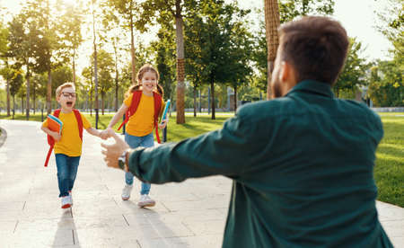 Man meets cheerful boy and girl with notebooks running into his arms while meeting children after school studies in park Stock Photo