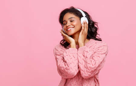 Happy young ethnic female smiling and listening to good music in headphones against pink background