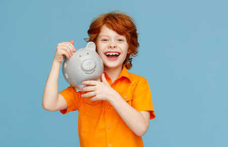 Happy redhead boy in orange shirt cheerfully smiling for camera and carrying piggy bank on shoulder against blue background