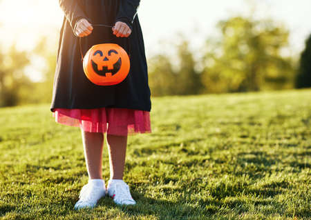 Unrecognizable girl in dress carrying jack o lantern basket while standing on lawn during Halloween celebration in park