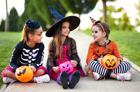 Cheerful friends in spooky costumes smiling and speaking with each other while sitting on path during Halloween celebration in evening in park