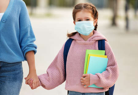 Positive schoolgirl in medical mask with backpack and copybooks holding hand of unrecognizable mom and looking at camera while walking on street