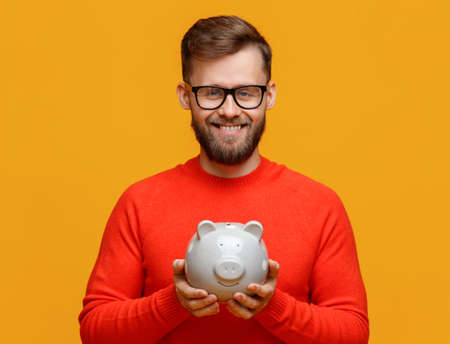 Happy bearded man in glasses smiling for camera and demonstrating piggy bank with savings isolated on yellow background