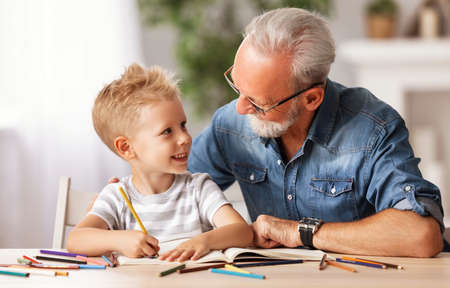 Happy boy smiling and looking at bearded elderly man while sitting at table and drawing picture in sketchbook