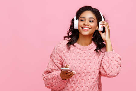 Delighted young ethnic female smiling and browsing social media on smartphone while listening to music against pink background