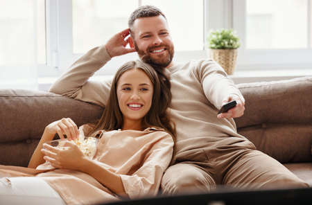 Happy family couple watching television at home on the sofa