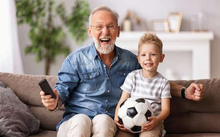 Happy senior grandfather and boy with ball screaming and celebrating goal while sitting on couch and watch football match on TV together