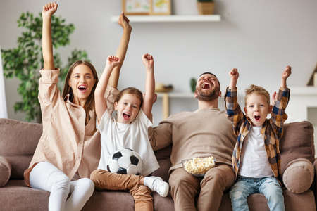 A family of fans mother father and children watching a football match and celebrating goal on TV at home