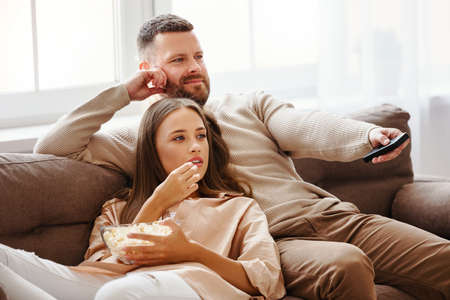 Family couple watching television at home on the sofa
