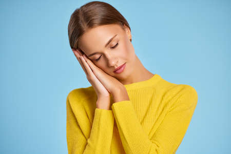 Beautiful female in yellow sweater clasping hands under cheek while pretending to sleep against blue background Imagens