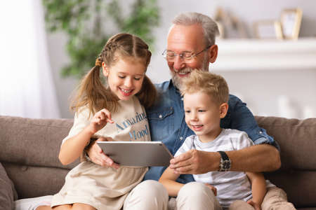 Happy family senior grandfather and grandchildren boy and girl sitting on sofa and watching cartoon on tablet on weekend day at home together Banco de Imagens