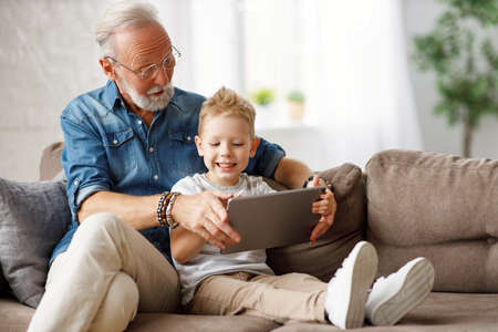 Happy family senior grandfather and boy sitting on sofa and watching cartoon on tablet on weekend day at home together