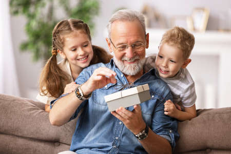 Happy family aged grandfather and grandchildren girl and boy opening gift box while resting on sofa during holiday celebration at home